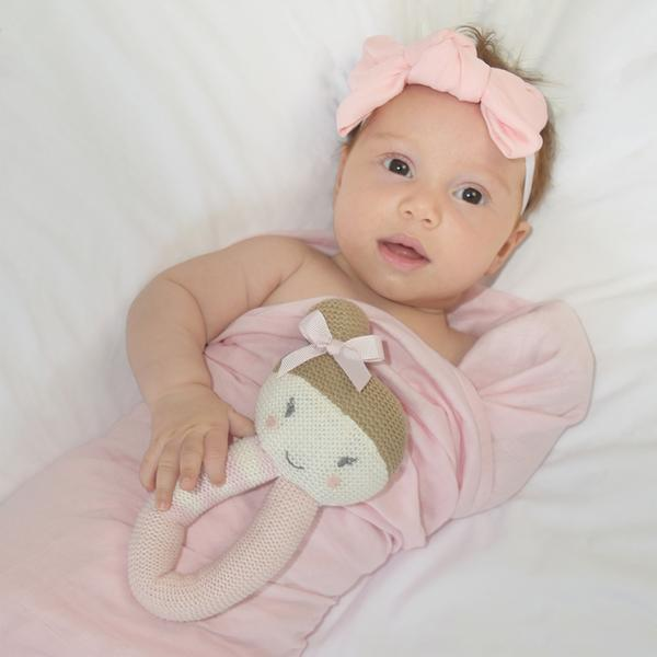 Baby-girl-with-ballerina-rattle-and-blush-muslin-swaddle-wrap-web-grande