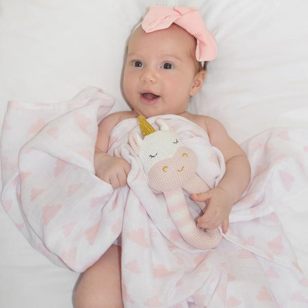 Baby-girl-with-unicorn-rattle-and-blush-cloud-muslin-swaddle-web-grande
